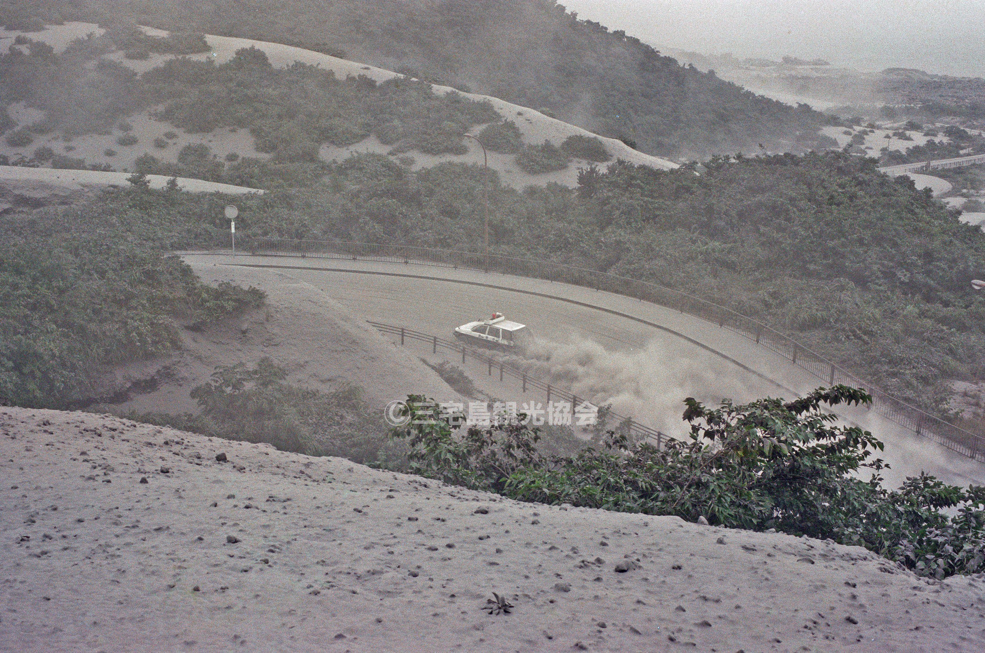 【2000(平成12)年噴火】 白煙をあげて走るパトカー